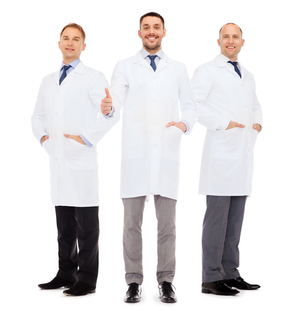 white coats: healthcare, profession and medicine concept - smiling male doctors in white coats over white background