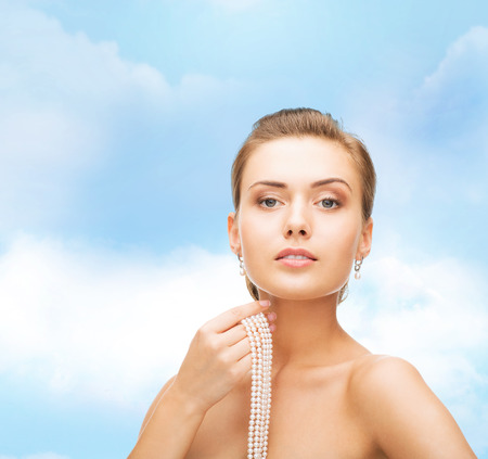 bride bangle: beauty, people and jewelry concept - beautiful woman with pearl earrings and necklace over blue cloudy sky background