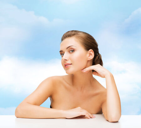 jeune fille adolescente nue: beauty, health and people concept - smiling beautiful woman with clean perfect skin over blue cloudy sky background Banque d'images
