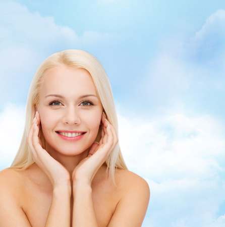 touching face: health and beauty concept - beautiful woman touching her face skin