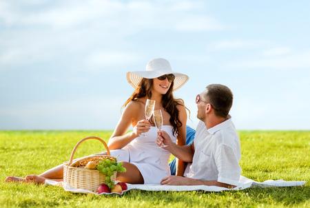 brindisi spumante: amore, incontri, le persone e le vacanze concetto - sorridente coppia bevendo champagne sul picnic nel cielo blu e sfondo di erba