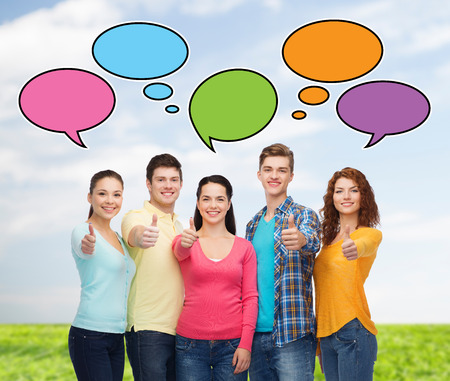 comment: friendship, communication, gesture and people concept - group of smiling teenagers showing thumbs up over sky and grass with text bubbles