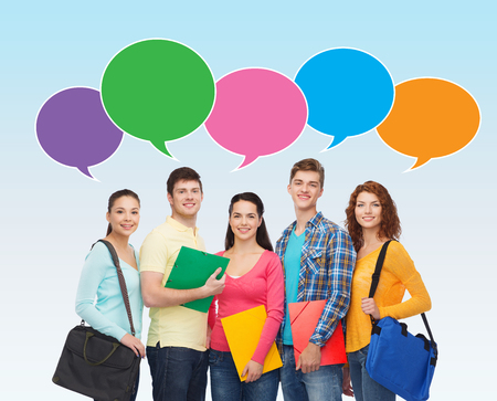school, education, communication and people concept - group of smiling students with folders and school bags over blue background with text bubbles photo