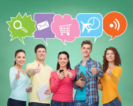 people, communication, school, gesture and technology concept - smiling friends with smartphones and tablet pc computers showing thumbs up over green board background with doodles photo