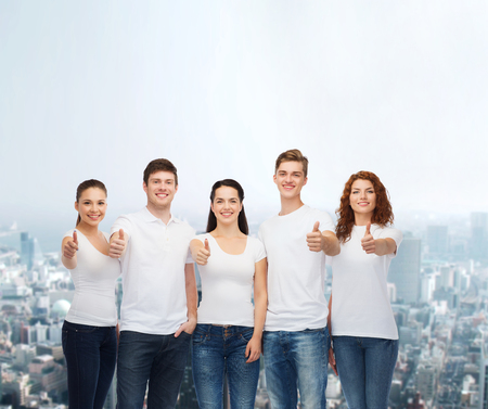 approvement: advertising, friendship, and people concept - group of smiling teenagers in white blank t-shirts showing thumbs up over city background