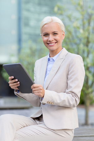 business, education, technology and people concept - smiling businesswoman working with tablet pc computer on city street photo