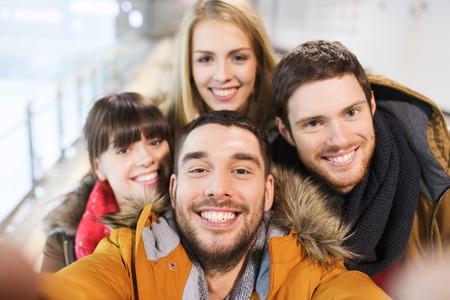 with friends: la gente, la amistad, la tecnolog�a y el concepto de ocio - amigos felices que toman Autofoto con c�mara o un tel�fono inteligente en pista de patinaje