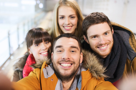 people, friendship, technology and leisure concept - happy friends taking selfie with camera or smartphone on skating rink Banco de Imagens
