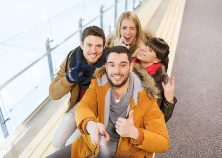 stick: people, friendship, technology and leisure concept - happy friends taking selfie with camera or smartphone and selfie stick on skating rink