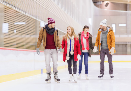 rink: people, friendship, sport and leisure concept - happy friends on skating rink