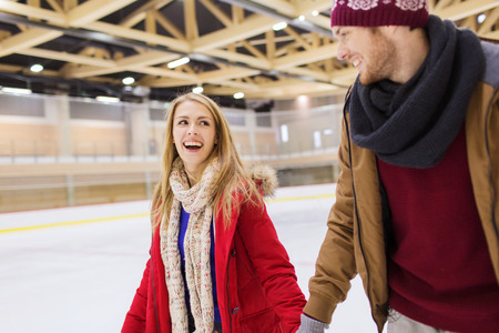 skating fun: people, friendship, sport and leisure concept - happy couple holding hands on skating rink