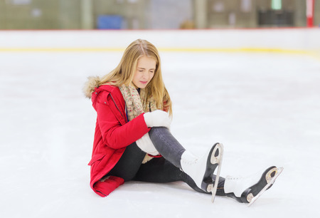 people, sport, trauma, pain and leisure concept - young woman fell down on skating rink and holding to her knee photo