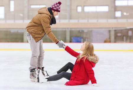 personas ayudando: la gente, la amistad, el deporte y el ocio concepto - hombre sonriente ayudar a las mujeres se levanten en la pista de patinaje