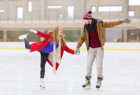 niño en patines: la gente, la amistad, el deporte y el concepto de ocio - feliz pareja cogidos de las manos en la pista de patinaje