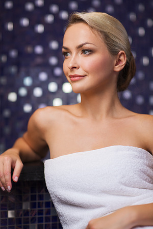 young woman sitting: people, beauty, spa, healthy lifestyle and relaxation concept - beautiful young woman sitting in bath towel