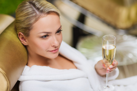 woman relaxing: people, beauty, lifestyle, holidays and relaxation concept - beautiful young woman in white bath robe lying on chaise-longue and drinking champagne at spa