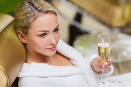 lifestyle: persone, bellezza, stile di vita, vacanze e relax concetto - giovane e bella donna in accappatoio bianco sdraiato su chaise-longue e bevendo champagne a spa Archivio Fotografico