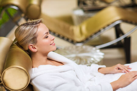 woman in bath: people, beauty, healthy lifestyle and relaxation concept - beautiful young woman lying on chaise-longue in bath robe at spa