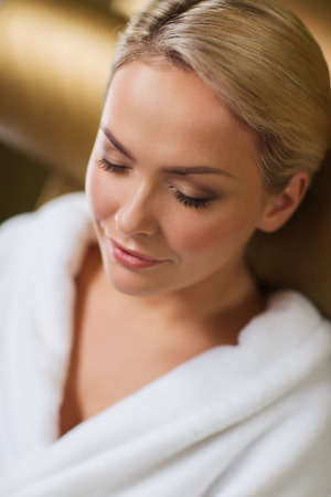 people, beauty, healthy lifestyle and relaxation concept - close up of beautiful young woman resting on chair in bath robe at spa photo