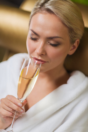 people, beauty, lifestyle, holidays and relaxation concept - beautiful young woman in white bath robe drinking champagne at spa photo