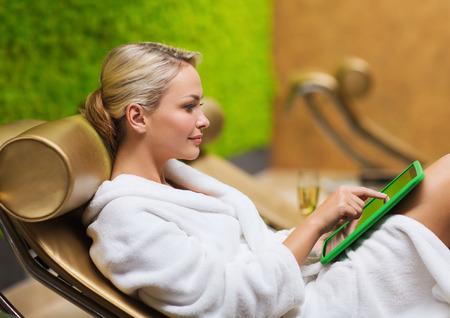 mensen, beauty, lifestyle, technologie en ontspanning concept - mooie jonge vrouw in witte badjas met tablet pc computer social networking in de spa Stockfoto