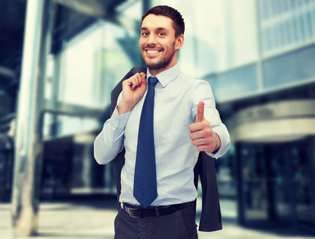 look up: business and office concept - handsome buisnessman with jacket over shoulder showing thumbs up