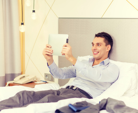 business, technology, internet and hotel concept - happy businessman with tablet pc computer lying in hotel in bed photo
