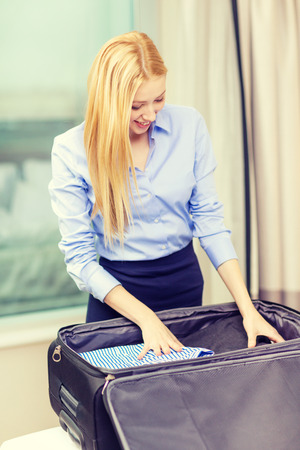 'young things': business, technology, internet and hotel concept - happy businesswoman packing things in suitcase in hotel room Stock Photo
