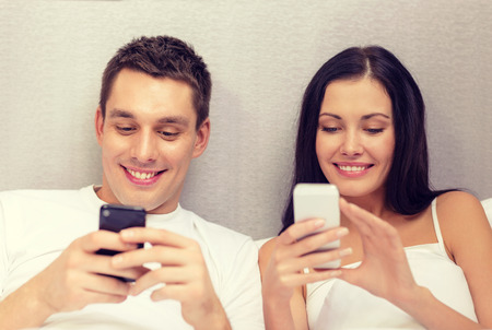 lovers in bed: hotel, travel, relationships, technology, intermet and happiness concept - smiling couple in bed with smartphones