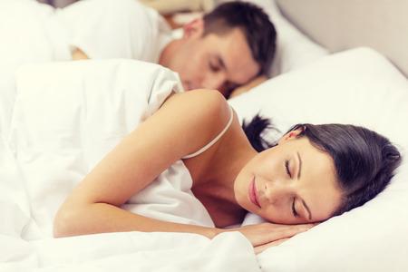 гостиница, поездка, отношения и счастье понятие - счастливая пара спит в постели