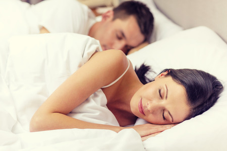 sleeping rooms: hotel, travel, relationships, and happiness concept - happy couple sleeping in bed