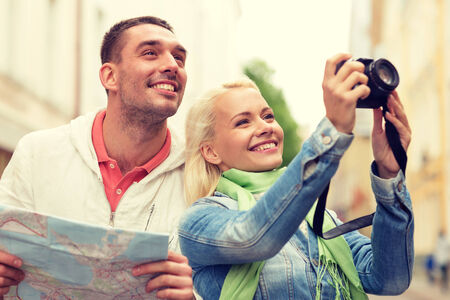 travel, vacation, technology and friendship concept - smiling couple with map and photocamera exploring city photo