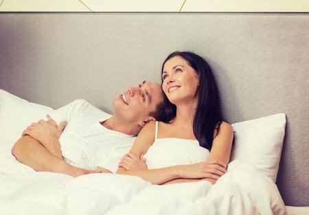 matrimonio feliz: hoteles, viajes, relaciones, felicidad y concepto - pareja feliz soñando en la cama