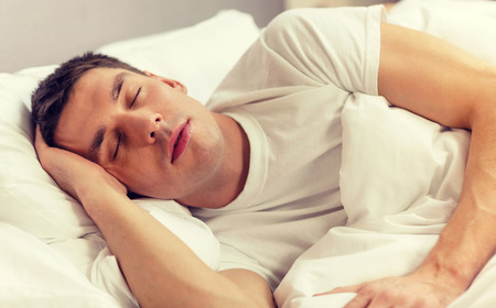 bed: hotel, travel and happiness concept - handsome man sleeping in bed Stock Photo