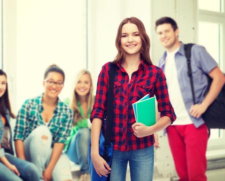 vysoká škola: vzdělávání a lidé koncepce - usmívající se studentka s přenosným tašku a notebooky