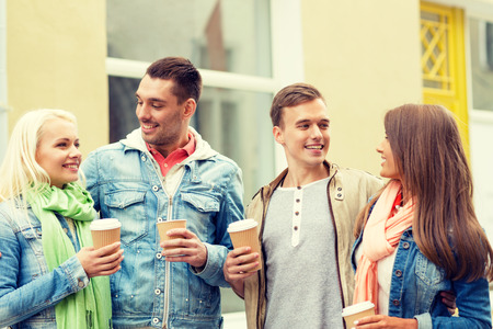 speak out: friendship, travel, drink and vacation concept - group of smiling friends with take away coffee