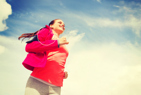 fitness, sport and lifestyle concept - smiling young woman with earphones running outdoors photo