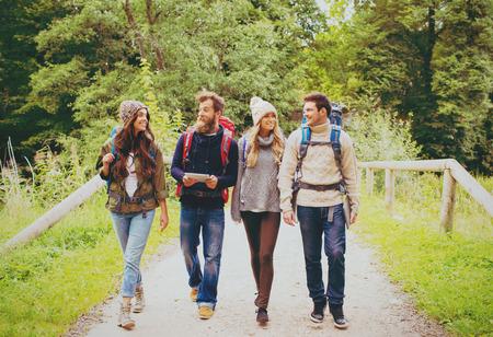 冒険、旅行、観光、ハイキング、人々 の概念 - バックパックやタブレット pc コンピューター歩いて屋外で笑顔の友人のグループ 写真素材