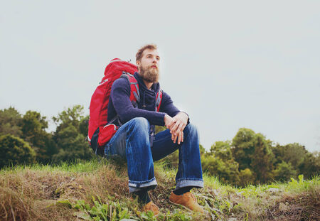 sitting on the ground: adventure, travel, tourism, hike and people concept - smiling man with red backpack sitting on ground