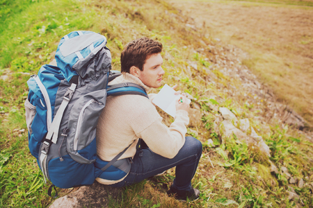 sitting on the ground: adventure, travel, tourism, hike and people concept - man with backpack sitting on ground from back