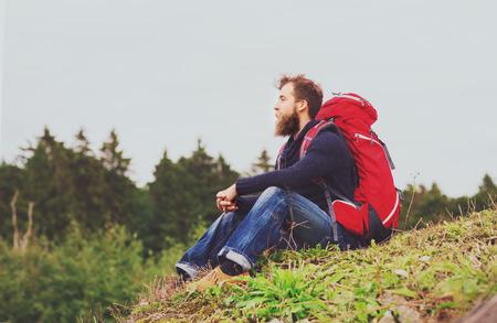 모험, 여행, 관광, 하이킹 및 사람들이 개념 - 수염 및 빨간색 배낭 땅에 앉아 남자