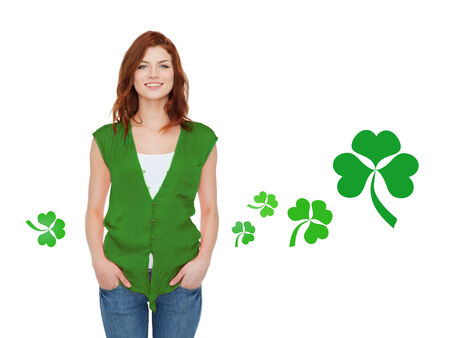 celtic shamrock: gestures, holidays, st. patricks day and people concept - happy teenager in green vest over white background with shamrock or clover