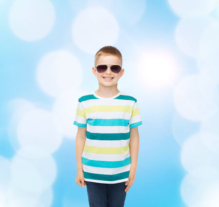 happiness, summer, childhood and people concept - smiling cute little boy in sunglasses over blue background photo