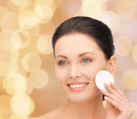 swab: beauty, people and health concept - beautiful smiling woman cleaning face skin with cotton pad over beige lights backgroundd Stock Photo
