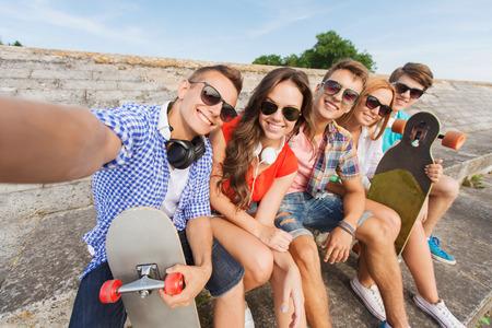 amicizia: amicizia, il tempo libero, l'estate, la tecnologia e la gente il concetto - gruppo di amici sorridenti con il pattino making selfie all'aperto Archivio Fotografico