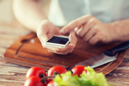 finger food: cooking, technology and home concept - closeup of man pointing finger to smartphone