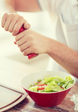 flavouring: cooking and home concept - close up of male hands flavouring salad in a bowl Stock Photo