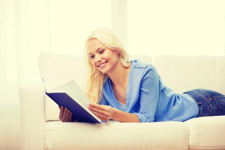 leasure: leasure e il concetto di casa - sorridente donna leggendo il libro e disteso sul divano a casa Archivio Fotografico