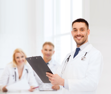 health professionals: medicine, profession, and healthcare concept - smiling male doctor with clipboard and stethoscope writing prescription over white background