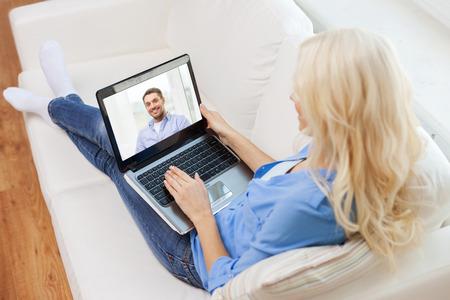ソファに座っていると自宅のラップトップ コンピューターとのチャットの女性を笑顔 - 家、技術、通信、人々 の概念